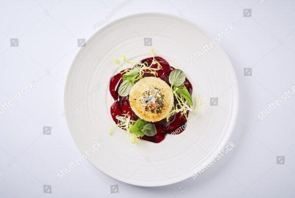 Десерт на красном конфитюре и белой тарелке